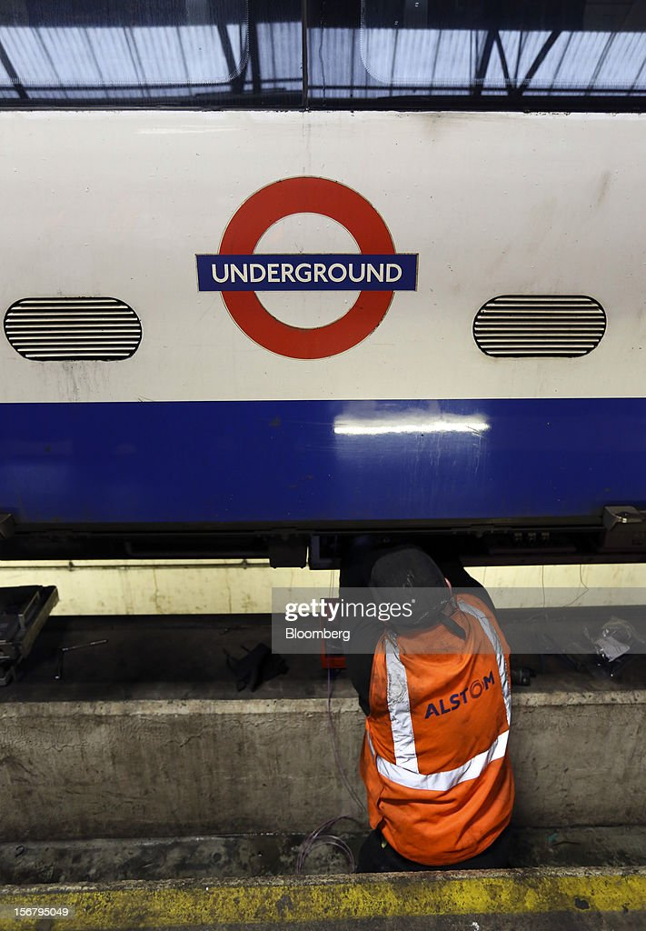 An employee works beneath the carriage of a London Underground Northern Line train at Alstom SA's Traincare Centre in the Golders Green district of London, U.K., on Wednesday, Nov. 21, 2012. Transport for London (TFL), who oversee the U.K. capital's public transport system, issued 300 million pounds ($476 million) of bonds five months ahead of schedule to take advantage of investor demand as it continues its 35 billion-pound transport investment program. Photographer: Chris Ratcliffe/Bloomberg via Getty Images