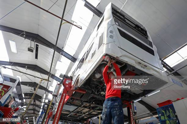An employee works beneath the engine compartment of an Enviro 400 London bus at the Alexander Dennis Ltd factory in Scarborough UK on Wednesday Sept...