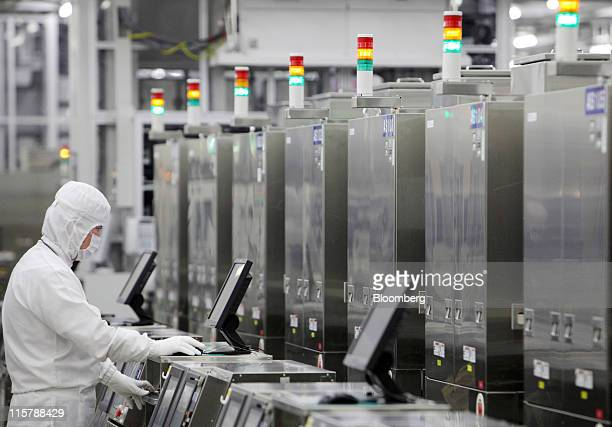 An employee works in a clean room on the production line for 300mm wafers at Renesas Electronics Corp's Naka plant in Hitachinaka city Ibaraki...