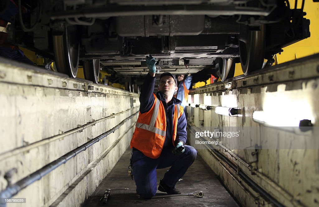 An employee works in an inspection pit beneath a London Underground Northern Line train at Alstom SA's Traincare Centre in the Golders Green district of London, U.K., on Wednesday, Nov. 21, 2012. Transport for London (TFL), who oversee the U.K. capital's public transport system, issued 300 million pounds ($476 million) of bonds five months ahead of schedule to take advantage of investor demand as it continues its 35 billion-pound transport investment program. Photographer: Chris Ratcliffe/Bloomberg via Getty Images