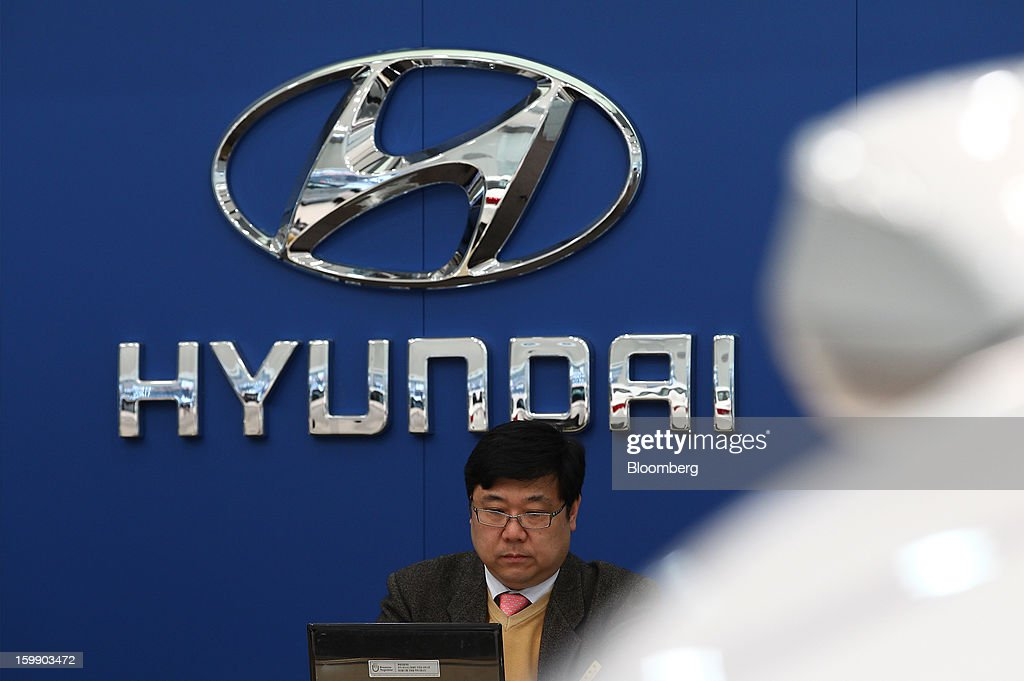 An employee works in front of a Hyundai Motor Co. logo displayed at a dealership in Seoul, South Korea, on Tuesday, Jan. 22, 2013. Hyundai Motor Co. is scheduled to release fourth-quarter earnings on Jan. 24. Photographer: SeongJoon Cho/Bloomberg via Getty Images