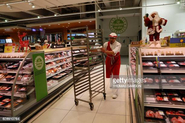 An employee works in the meat section of an hypermarket store of French retail giant Carrefour in Villeneuvelagarenne near Paris on December 7 2016 /...