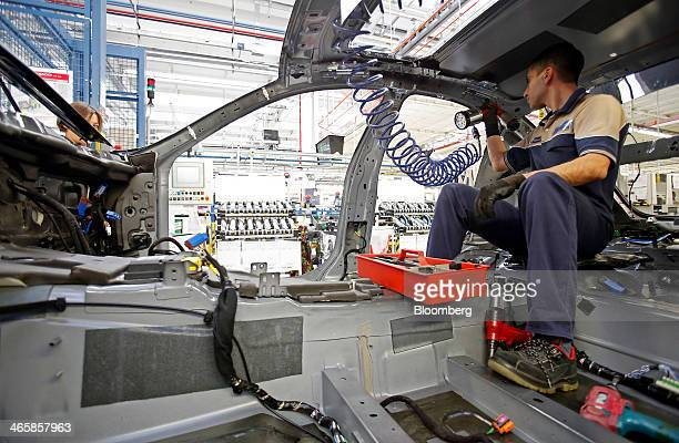 An employee works inside a Maserati Ghibli luxury automobile produced by Maserati SpA as it travels along the production line at Fiat SpA's...