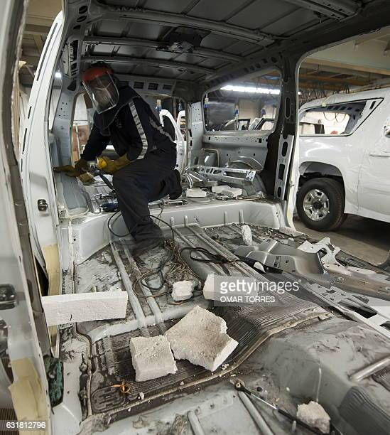 An employee works inside a SUV's dismantled chassis to armourplate the vehicle on May 2 2011 at an armor plating company in Mexico City The...