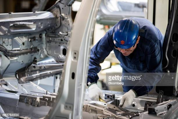 An employee works inside an automobile body frame on the production line inside the Suzuki Motor Corp plant in Esztergom Hungary on Monday May 15...