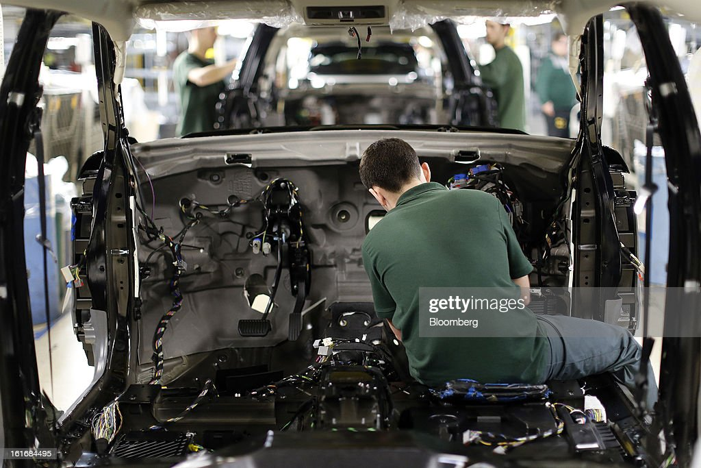 An employee works inside the body shell of a Range Rover Evoque SUV automobile, produced by Jaguar Land Rover Plc, a unit of Tata Motors Ltd., as it travels along the production line at the company's assembly plant in Halewood, U.K., on Wednesday, Feb. 13, 2013. Carmakers from Ford Motor Co. to Audi AG and Jaguar Land Rover Plc are using record amounts of aluminium to replace heavier steel, providing relief to producers of the metal confronting excess supplies and depressed prices. Photographer: Simon Dawson/Bloomberg via Getty Images