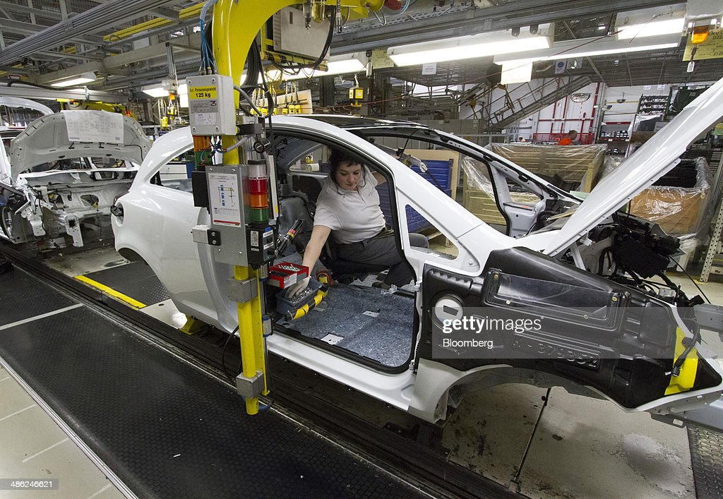 An employee works inside the chassis of an Opel Corsa automobile on the production line at the Adam Opel AG factory, operated by General Motors Co. (GM), in Eisenach, Germany, on Wednesday, April 23, 2014. European sales at Opel and its U.K. sister brand Vauxhall gained 8.5 percent to 226,888 cars in the first quarter, slightly better than the 8.1 percent increase for the market overall, according to ACEA data. Photographer: Martin Leissl/Bloomberg via Getty Images