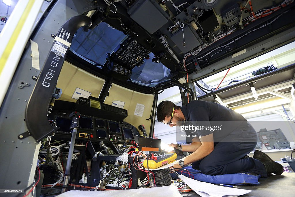 An employee works inside the cockpit of a Super Lynx 300 helicopter, produced by AgustaWestland, a unit of Finmeccanica SpA, at the company's plant in Yeovil, U.K., on Thursday, June 12, 2014. U.K. unemployment declined more than expected and industrial production rose at the fastest annual pace since 2011, according to reports released this week. Photographer: Chris Ratcliffe/Bloomberg via Getty Images