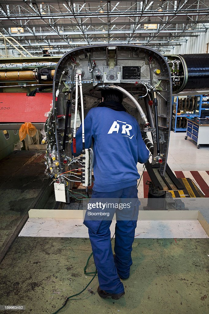 An employee works inside the engine housing of an ATR-72 turboprop aircraft, manufactured by Avions de Transport Regional (ATR), at the company's production facility in Colomiers, France, on Wednesday, Jan. 23, 2013. ATR, the world's largest maker of turbo-propeller airliners, reported record profit for 2012, even as it fell short of its shipment target amid production delays. Photographer: Balint Porneczi/Bloomberg via Getty Images