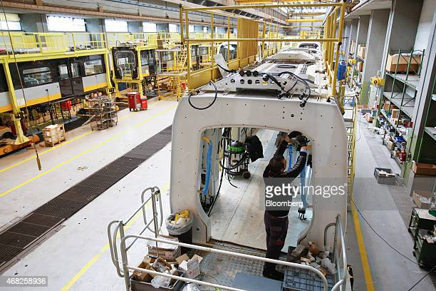 An employee works inside the shell of a Copenhagen metro train carriage during manufacture at AnsaldoBreda SpA's rail car plant in Naples Italy on...