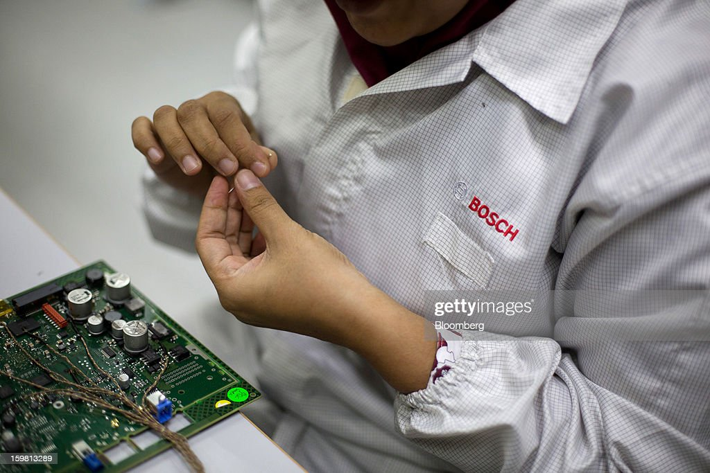 An employee works on a circuit board for the General Motors NextGen Navigation Processing Unit, produced by Robert Bosch GmbH for General Motors Co. (GM), on the production line at the Robert Bosch plant in the Bayan Lepas Industrial Zone on Penang Island, Malaysia, on Thursday, Jan. 17, 2013. Robert Bosch GmbH is the world's largest automotive supplier. Photographer: Lam Yik Fei/Bloomberg via Getty Images