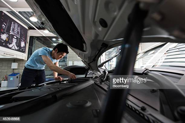 An employee works on a customized Bayerische Motoren Werke AG 1 Series 118d vehicle at the ASeung Automotive Group garage in Seoul South Korea on...