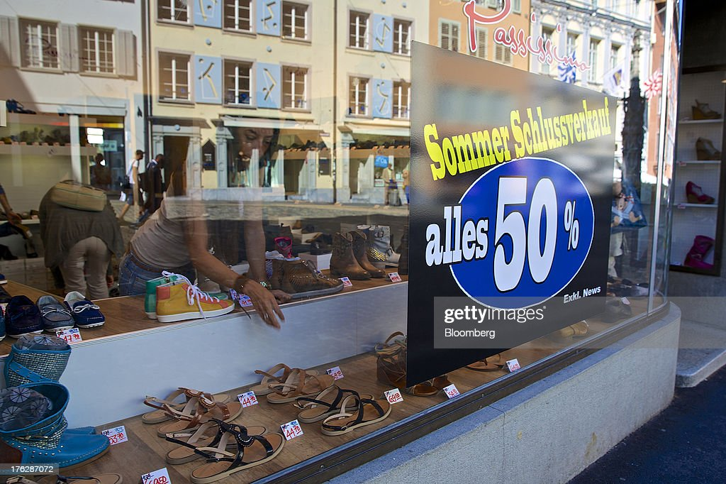 An employee works on a display of shoes near a poster advertising a sale in the window of a footware store in Lucerne, Switzerland, on Saturday, Aug. 10, 2013. The Swiss National Bank will abolish its franc ceiling once it starts raising interest rates, Vice President Jean-Pierre Danthine said. Photographer: Gianluca Colla/Bloomberg via Getty Images