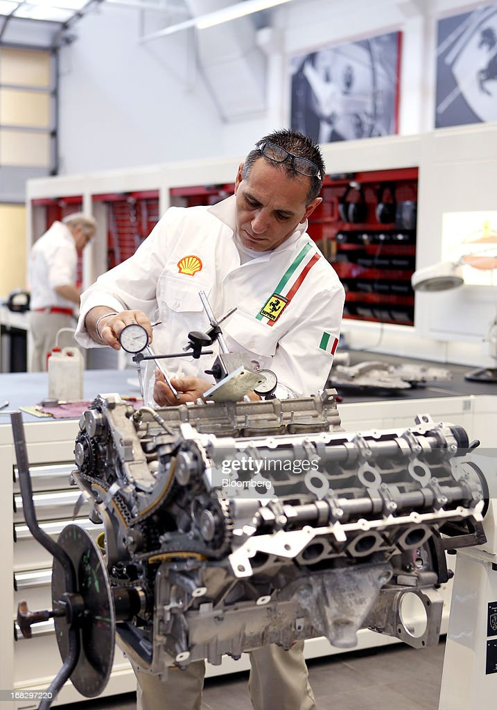 An employee works on a Ferrari F430 engine in the vintage cars workshop at Ferrari SpA's automobile plant in Maranello, Italy, on Wednesday, May 8, 2013. Ferrari SpA, the Italian supercar manufacturer owned by Fiat SpA, plans to reduce sales to fewer than 7,000 vehicles this year to 'maintain the exclusivity' of the brand. Photographer: Alessia Pierdomenico/Bloomberg via Getty Images