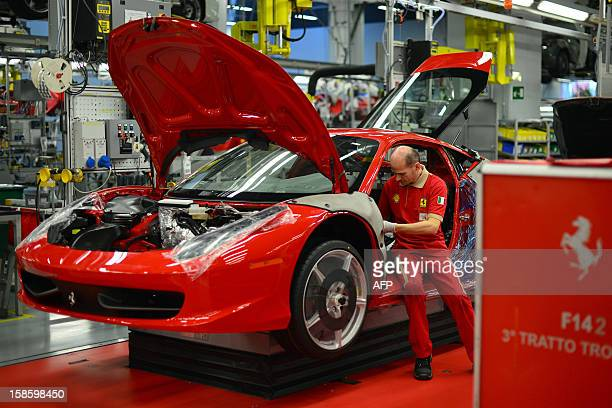 An employee works on a Ferrari tourism car in the Ferrari factory on December 5 2012 in Maranello The Ferrari 45 buildings's factory where more than...