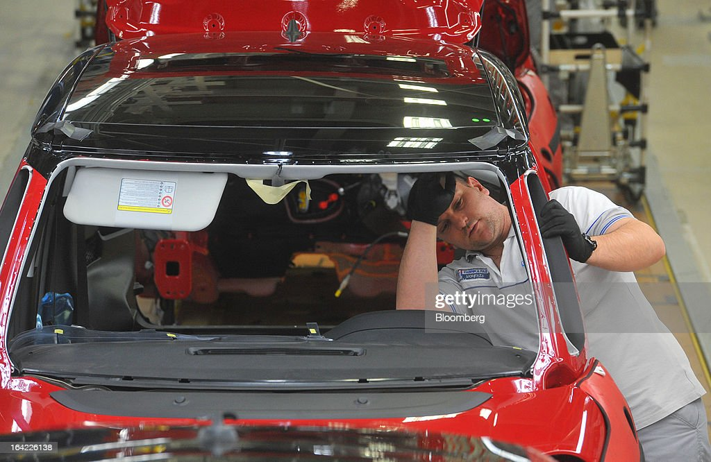 An employee works on a Fiat 500L automobile during assembly on the production line at the Fiat Automobili Srbija plant in Kragujevac, Serbia, on Wednesday, March 20, 2013. Fiat Automobili Srbija, a joint venture between the government and Italian carmaker Fiat, is Serbia's sole automaker. Photographer: Oliver Bunic/Bloomberg via Getty Images
