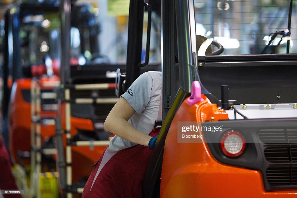 An employee works on a Linde H30 forklift truck as its sits on the production line at the Linde Material Handling GmbH factory, a unit of Kion Group AG, in Aschaffenburg, Germany, on Tuesday, Nov. 12, 2013. Kion Group AG, the German forklift-maker which listed shares in June, is looking to expand its global sales network via acquisitions to catch up with main competitor Toyota Industries Corp. Photographer: Krisztian Bocsi/Bloomberg via Getty Images