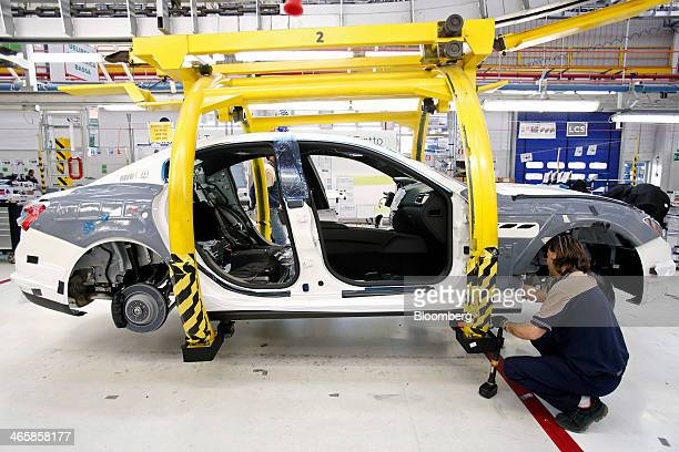 An employee works on a Maserati Ghibli luxury automobile produced by Maserati SpA as it travels along the production line at Fiat SpA's Grugliasco...