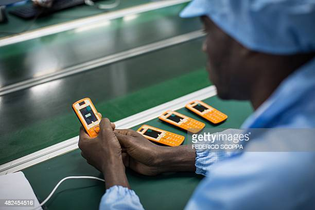 An employee works on a mobile phone on the assembly line at the VMK factory in Brazzaville on July 20 2015 The factory run by Verone Mankou produces...