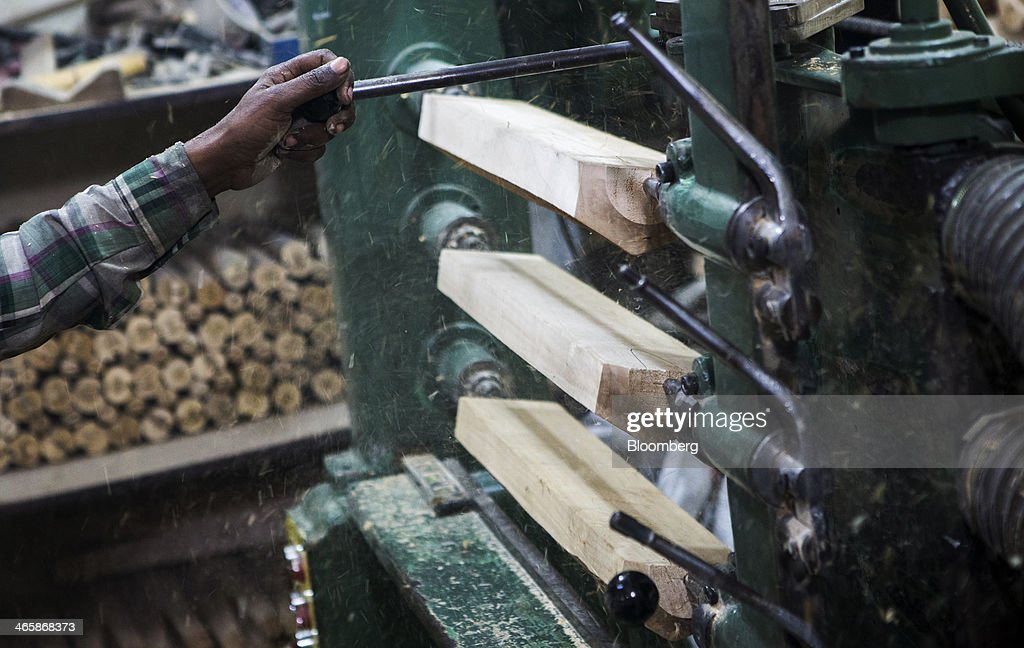 An employee works on a multiple bat cutting machine at a Stanford Cricket Industries factory in Meerut, Uttar Pradesh, India, on Wednesday, Jan. 29, 2014. The Indian Premier League (IPL), the worlds richest cricket competition, auction for IPL 2014 is scheduled to begin on Feb. 12 with the seasons first match to be played on April 8. Photographer: Prashanth Vishwanathan/Bloomberg via Getty Images