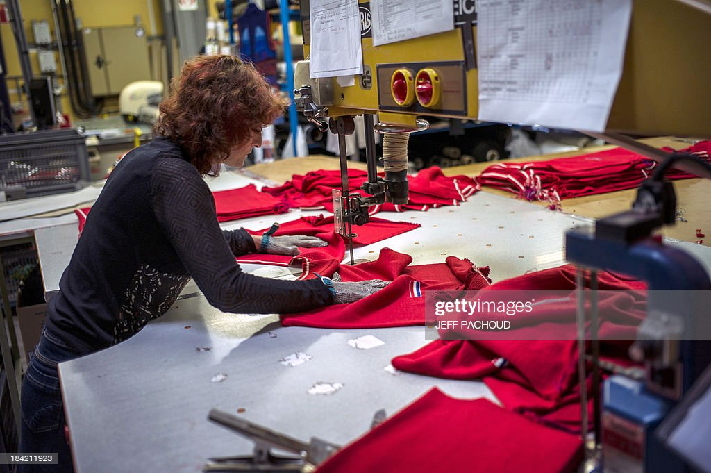 An employee works on a new French Ski School (ESF) red sweater on October 11, 2013 in a Degre 7 knitting workshop based in Le Creusot, eastern France. The brand will produce the popular red sweaters worn by ESF instructors, reconnecting the product with the 'Made in France' label.