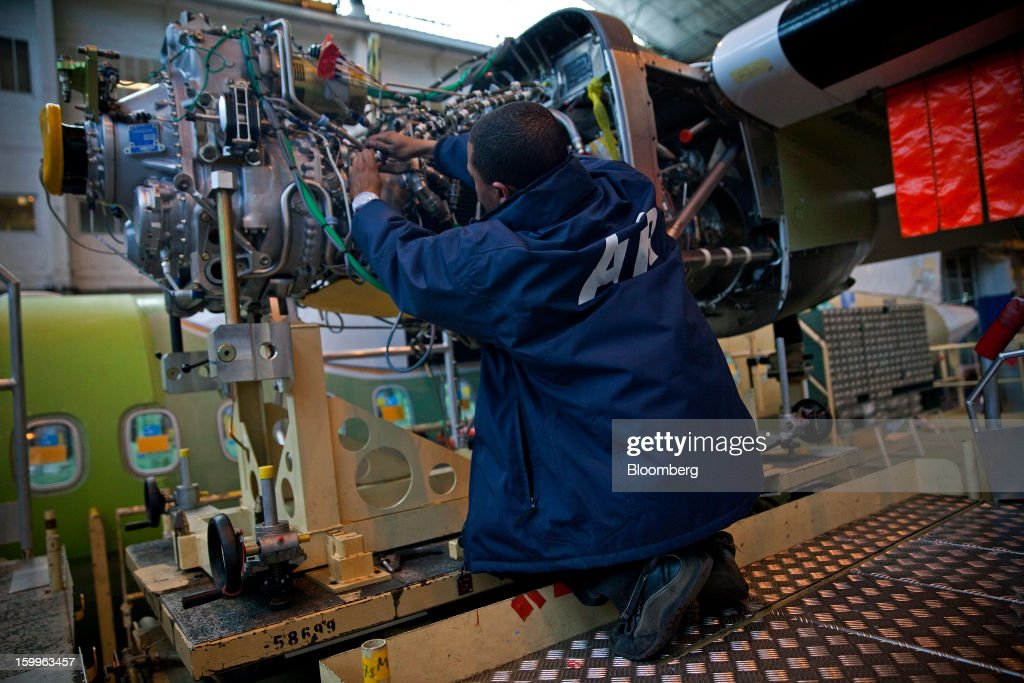 An employee works on a Pratt & Whitney engine during the construction of an ATR-72 turboprop aircraft, manufactured by Avions de Transport Regional (ATR), at the company's production facility in Colomiers, France, on Wednesday, Jan. 23, 2013. ATR, the world's largest maker of turbo-propeller airliners, reported record profit for 2012, even as it fell short of its shipment target amid production delays. Photographer: Balint Porneczi/Bloomberg via Getty Images