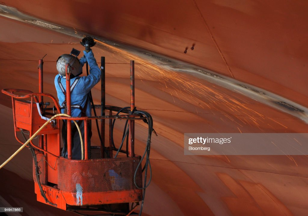 An employee works on a ship under construction at the Hyundai Heavy Industries Co shipyard in Ulsan South Korea on Thursday April 23 2009 Hyundai...