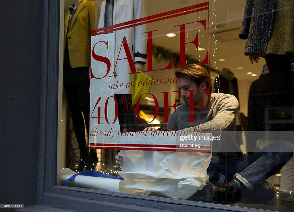 An employee works on a sign in the window of a Club Monaco store in the Soho neighborhood of New York, U.S., on Monday, Dec. 30, 2013. The failure of United Parcel Service Inc. (UPS) and FedEx Corp. to deliver packages in time for Christmas has exposed the perils of retailers promising to get last-minute gifts to customers. Photographer: Jin Lee/Bloomberg via Getty Images