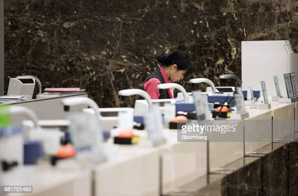 An employee works on a teller line at the Mizuho Bank Ltd branch inside the Mizuho Financial Group Inc headquarters in Tokyo Japan on Friday April 21...
