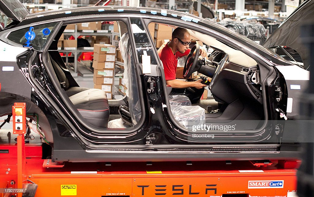 An employee works on a Telsa Motor Inc. Model S sedan as it makes its way along an assembly line at company's assembly plant in Fremont, California, U.S., on Wednesday, July 10, 2013. Tesla is building Model S electric sedans faster than its initial 400-a-week goal as demand and the companys production skills increase, Chief Executive Officer Elon Musk said. Photographer: Noah Berger/Bloomberg via Getty Images