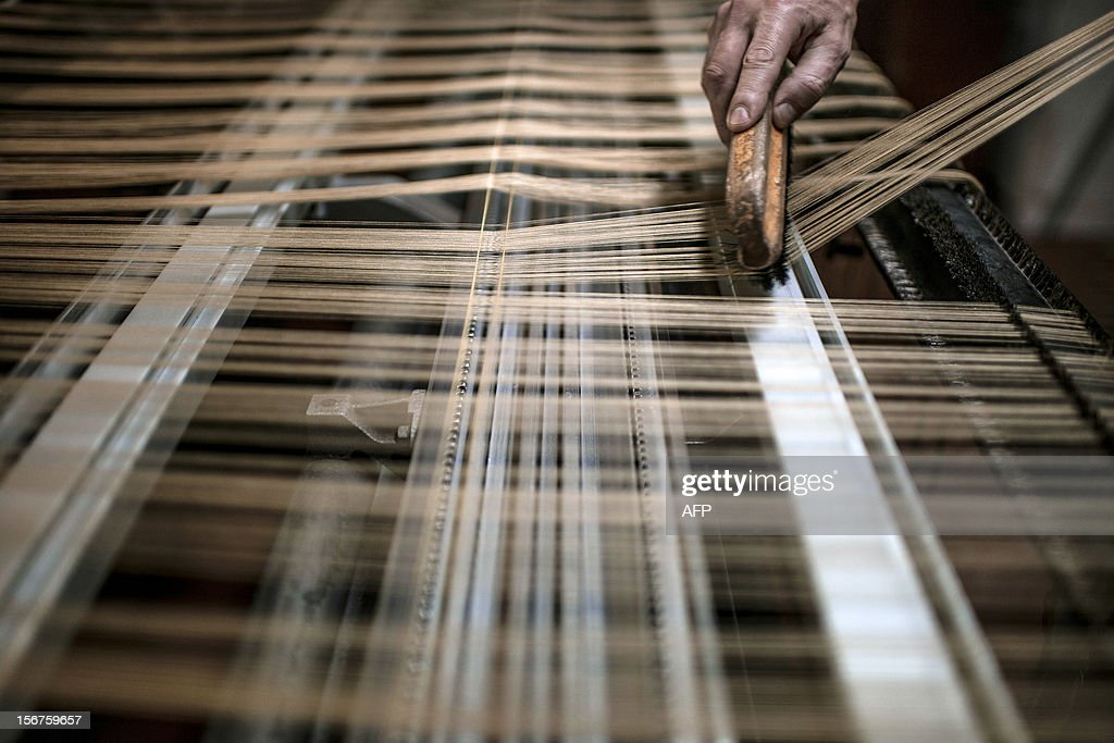 BOUILLON - An employee works on a weaving loom at the Tassinari & Chatel silk manufacture on November 8, 2012 in Lyon. Founded in 1865, Tassinari & Chatel produces furnishing fabrics, specialising in the high-end and luxury markets. AFP PHOTO / JEFF PACHOUD
