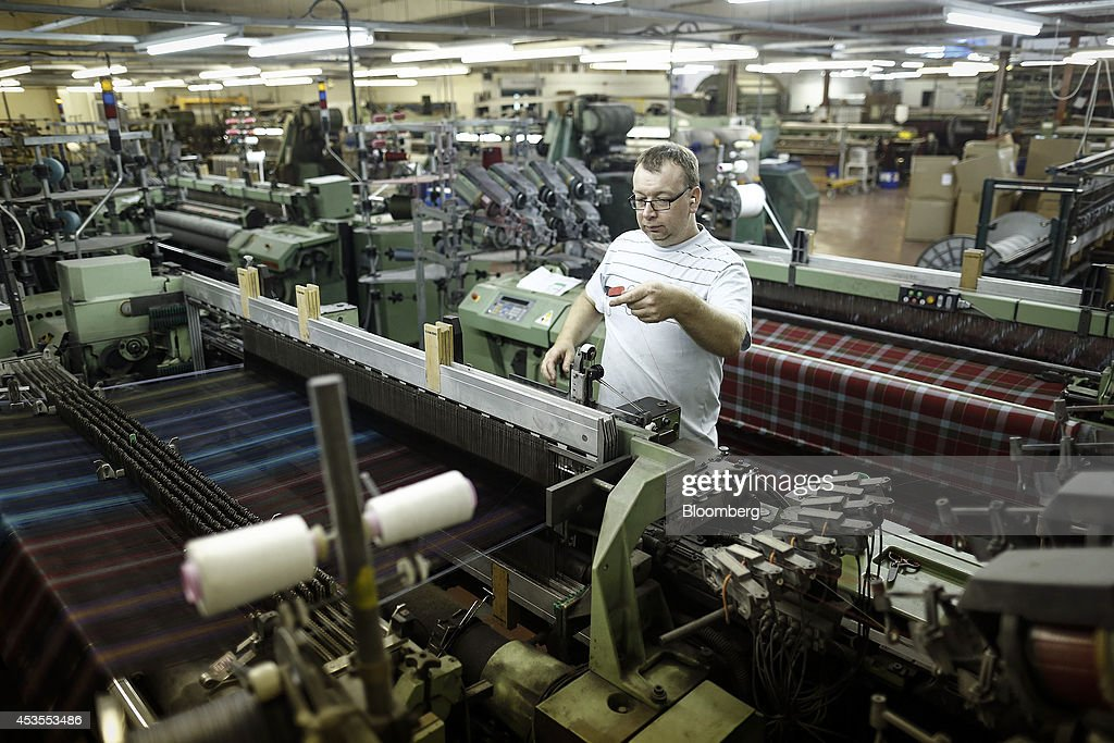 An employee works on a weaving machine during tartan material production at Lochcarron John Buchan Ltd.'s plant in Selkirk, U.K., on Tuesday, Aug. 12, 2014. Scottish nationalists seeking independence from the U.K. lost ground in the latest poll of voting intentions for the Sept. 18 referendum, as campaigners to keep the 307-year-old U.K. intact extended their lead. Photographer: Simon Dawson/Bloomberg via Getty Images