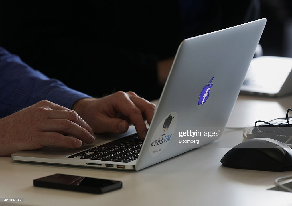 An employee works on an Apple Inc. laptop inside the Facebook Inc. Prineville Data Center in Prineville, Oregon, U.S., on Monday, April 28, 2014. The Facebook Prineville Data Center features leading energy-efficient technology, including features such as rainwater reclamation, a solar energy installation for providing electricity to the office areas and reuse of heat created by the servers to heat office space. Photographer: Meg Roussos/Bloomberg via Getty Images