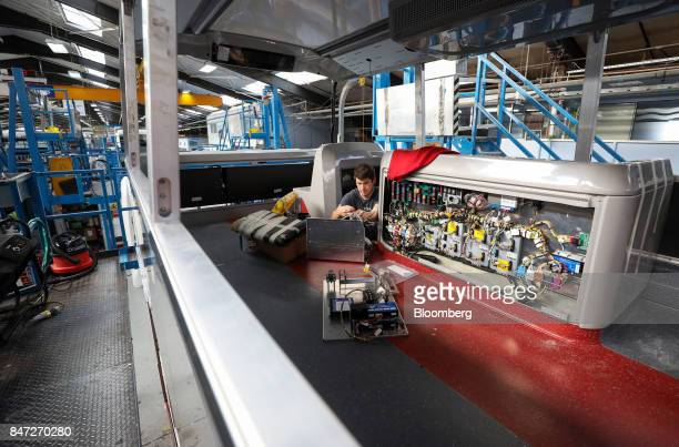 An employee works on an electrical components box on the upper deck of an Enviro 400 bus at the Alexander Dennis Ltd factory in Scarborough UK on...
