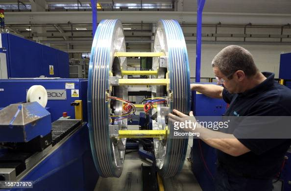 An employee works on an electrical wiring system for use in a Magnetic Resonance Imaging scanner at the Siemens AG Magnet Technology factory in...