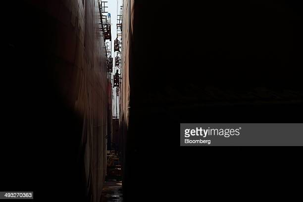 An employee works on an elevated work platform between ships under construction in the dry dock at the Hyundai Mipo Dockyard Co shipyard an affiliate...