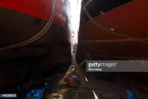 An employee works on an elevated work platform between two vessels under construction in the dry dock at the Hyundai Mipo Dockyard Co shipyard an...