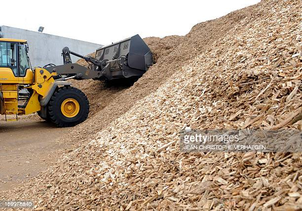 An employee works on an excavator at storing fuel composed of wood chips to be used for the UEM biomass plant in Metz eastern France on January 24...