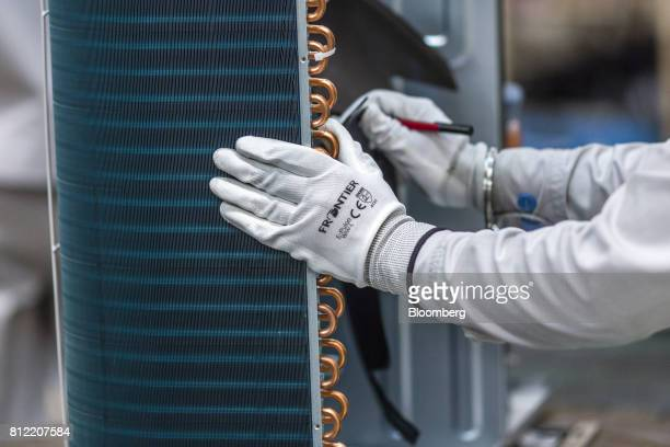 An employee works on an outdoor unit of a split system air conditioner on an assembly line at the Daikin Air Conditioning India Pvt factory in the...