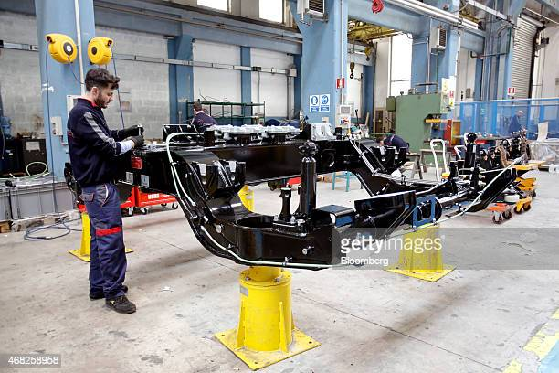 An employee works on components for a bogie chassis assembly during train carriage manufacturing at AnsaldoBreda SpA's rail car plant in Naples Italy...