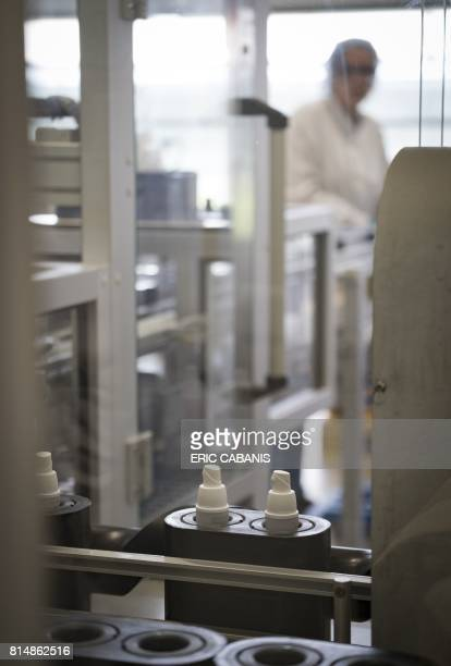 An employee works on cosmetic products on a production line at the plant of French multinational pharmaceutical and cosmetics company 'Pierre Fabre'...