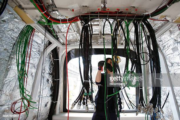 An employee works on electric cabling inside the shell of a Copenhagen metro train carriage during manufacture at AnsaldoBreda SpA's rail car plant...