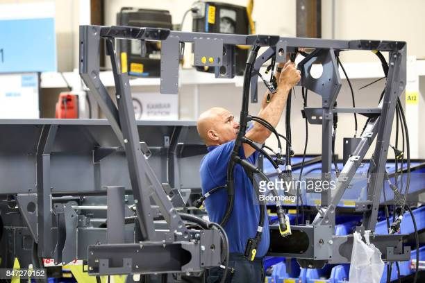 An employee works on electrical cabling on the chassis of an Enviro 200 bus under construction at the Alexander Dennis Ltd factory in Guildford UK on...