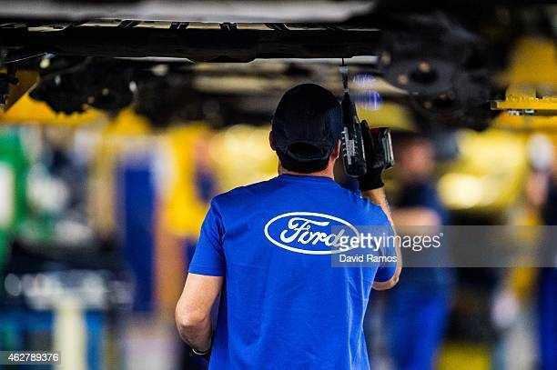 An employee works on Ford Mondeo vehicles on the production line during assembly at Ford plant in Almussafes on February 5 2015 in Valencia Spain The...