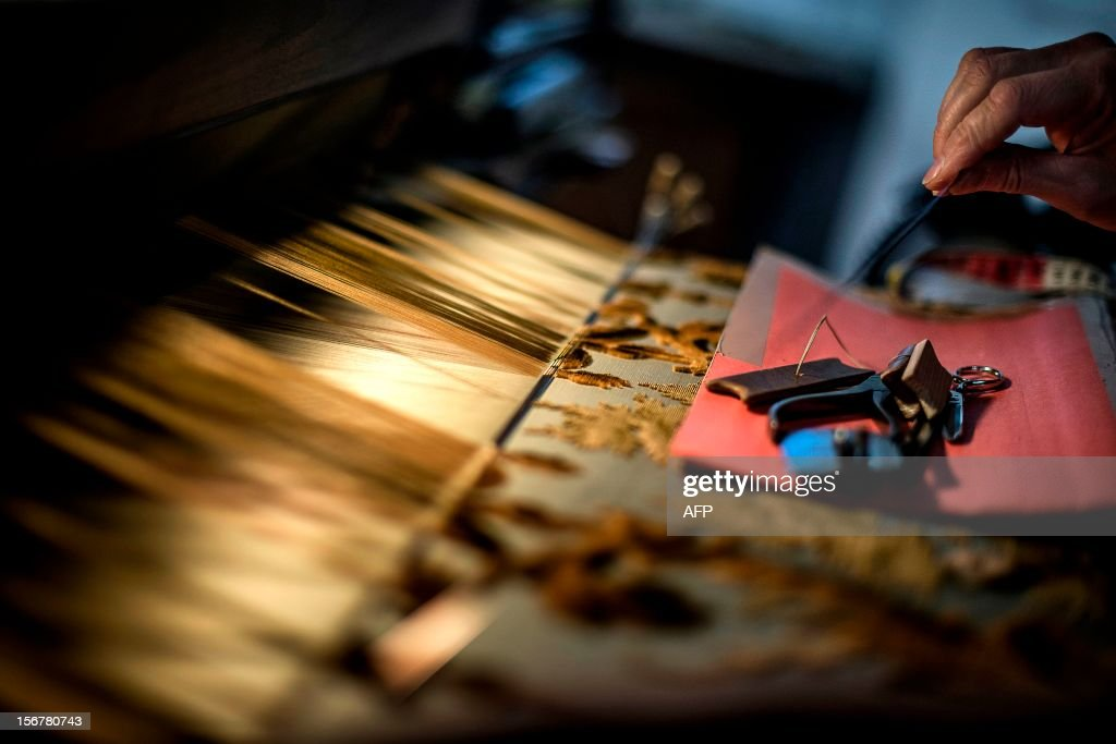 BOUILLON - An employee works on her weaving loom at the Tassinari & Chatel silk manufacture on November 8, 2012 in Lyon. Founded in 1865, Tassinari & Chatel produces furnishing fabrics, specialising in the high-end and luxury markets. AFP PHOTO / JEFF PACHOUD