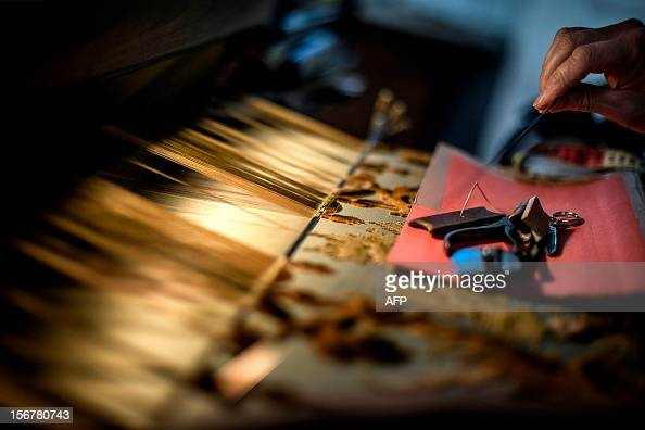 BOUILLON An employee works on her weaving loom at the Tassinari Chatel silk manufacture on November 8 2012 in Lyon Founded in 1865 Tassinari Chatel...