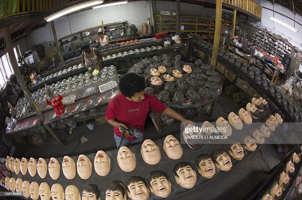 An employee works on masks of Brazilian football star Neymar, at the carnival masks factory Condal, in Sao Gonçalo, about 35 km from downtown Rio de Janeiro, on January 9, 2013. Rio's world famous carnival takes place February 9-12. AFP PHOTO/VANDERLEI ALMEIDA