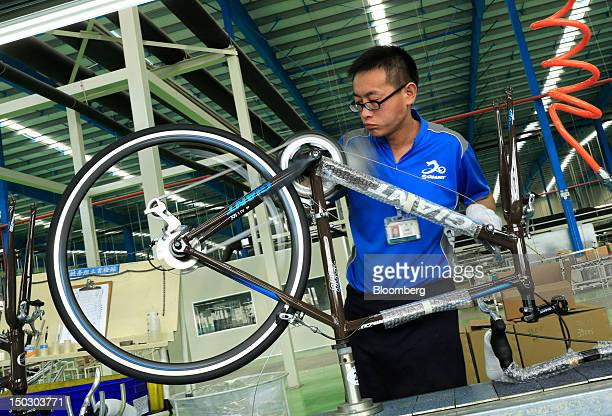 An employee works on the assembly of a bicycle drive train during manufacture process at the Giant Manufacturing Co Ltd factory in the Kunshan area...