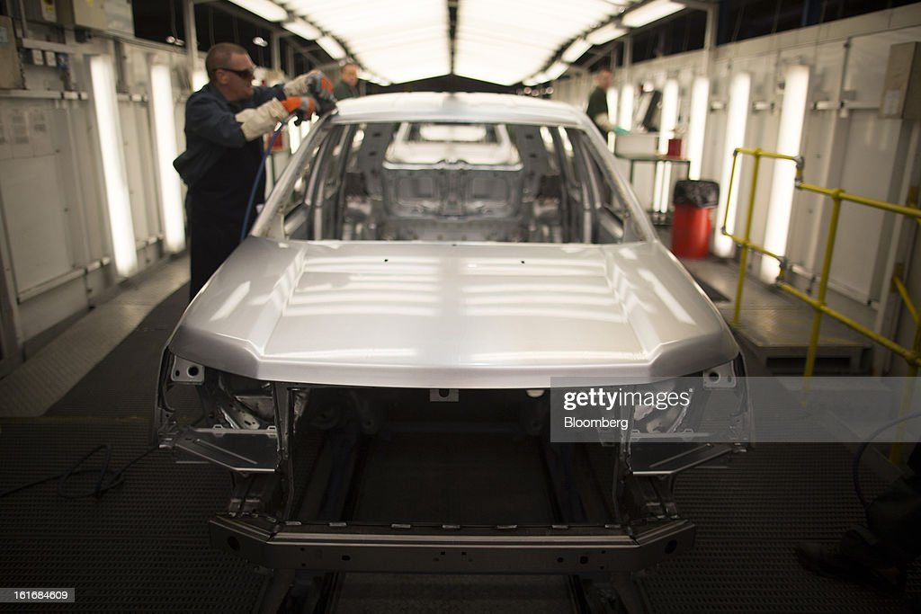 An employee works on the body shell of a Land Rover Freelander 2 SUV automobile, produced by Jaguar Land Rover Plc, a unit of Tata Motors Ltd., as it travels along the production line at the company's assembly plant in Halewood, U.K., on Wednesday, Feb. 13, 2013. Carmakers from Ford Motor Co. to Audi AG and Jaguar Land Rover Plc are using record amounts of aluminium to replace heavier steel, providing relief to producers of the metal confronting excess supplies and depressed prices. Photographer: Simon Dawson/Bloomberg via Getty Images