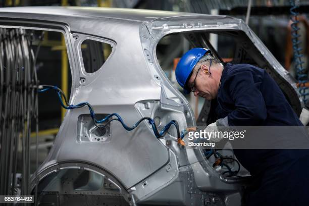 An employee works on the body shell of an automobile on the production line inside the Suzuki Motor Corp plant in Esztergom Hungary on Monday May 15...